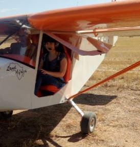 La escritora Déborah F. Muñoz pilotando una avioneta
